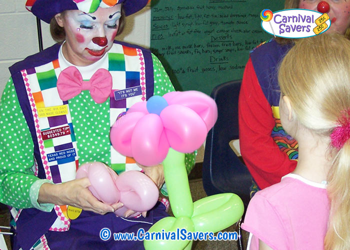 Balloon clown making shaped balloon for child at a carnival